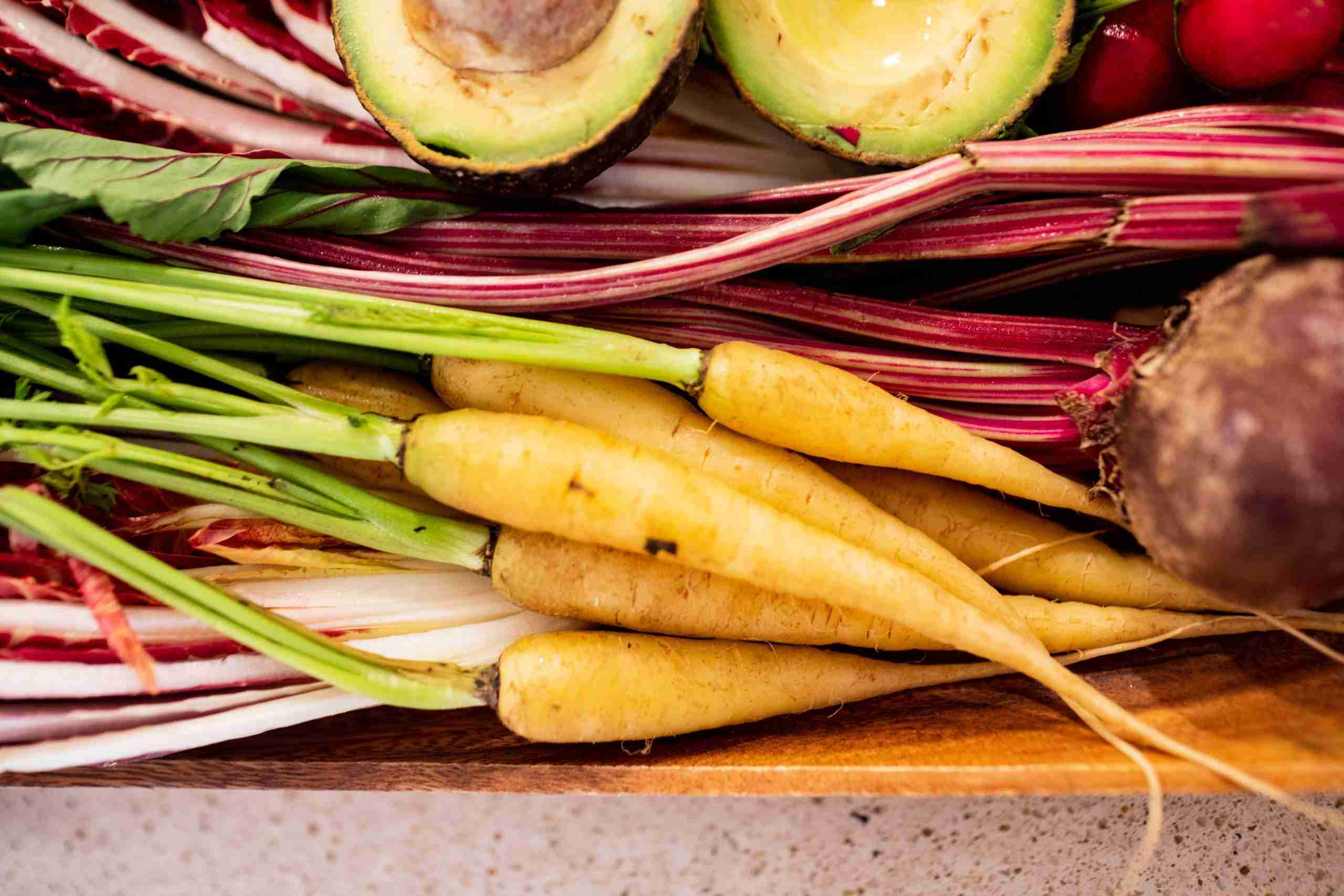 Wood bowl filled with orange carrots, red beets, radishes and an avocado.