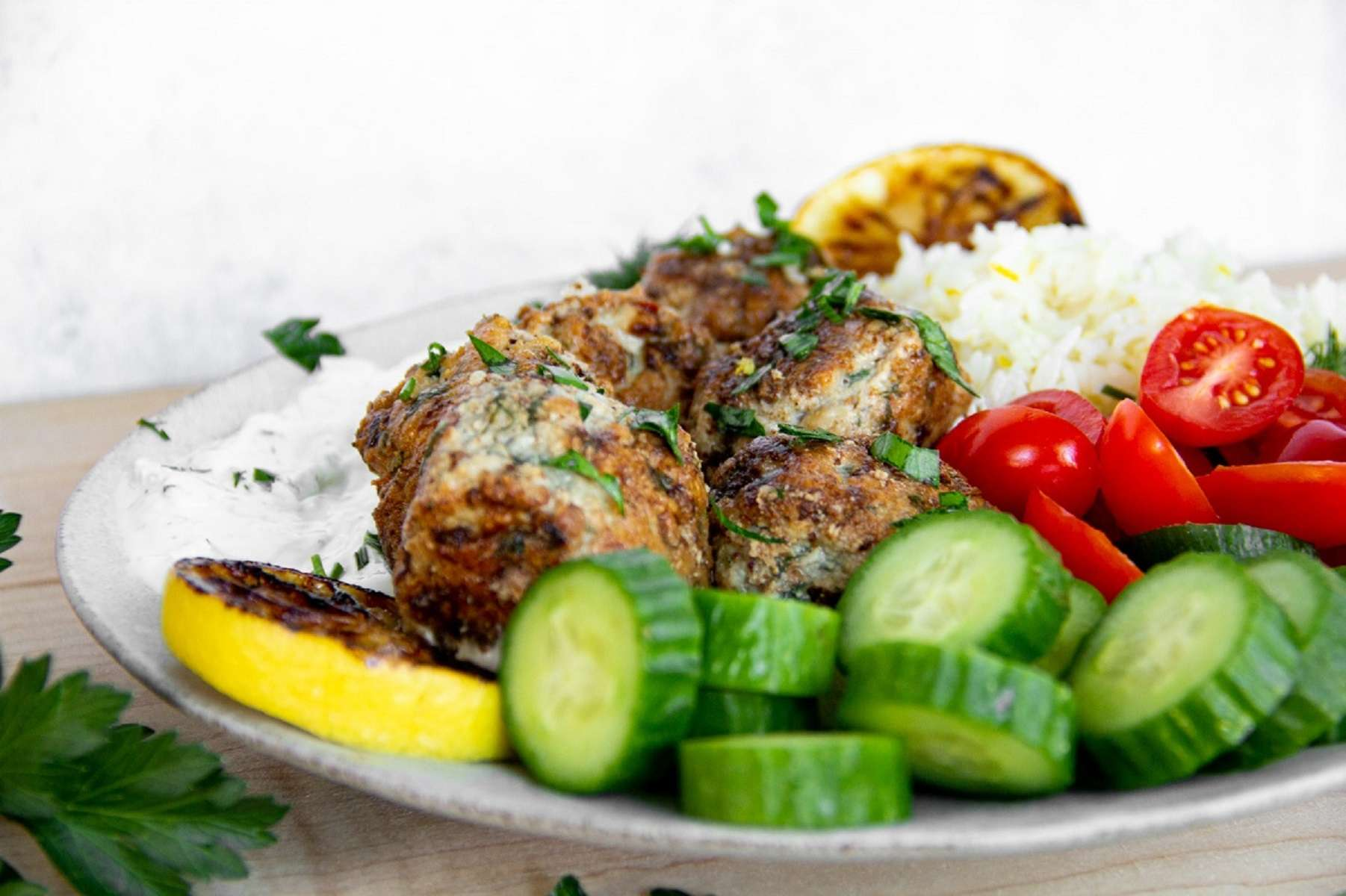 Up close picture of Greek meatballs with cucumber, tomatoes, and zesty lemon rice