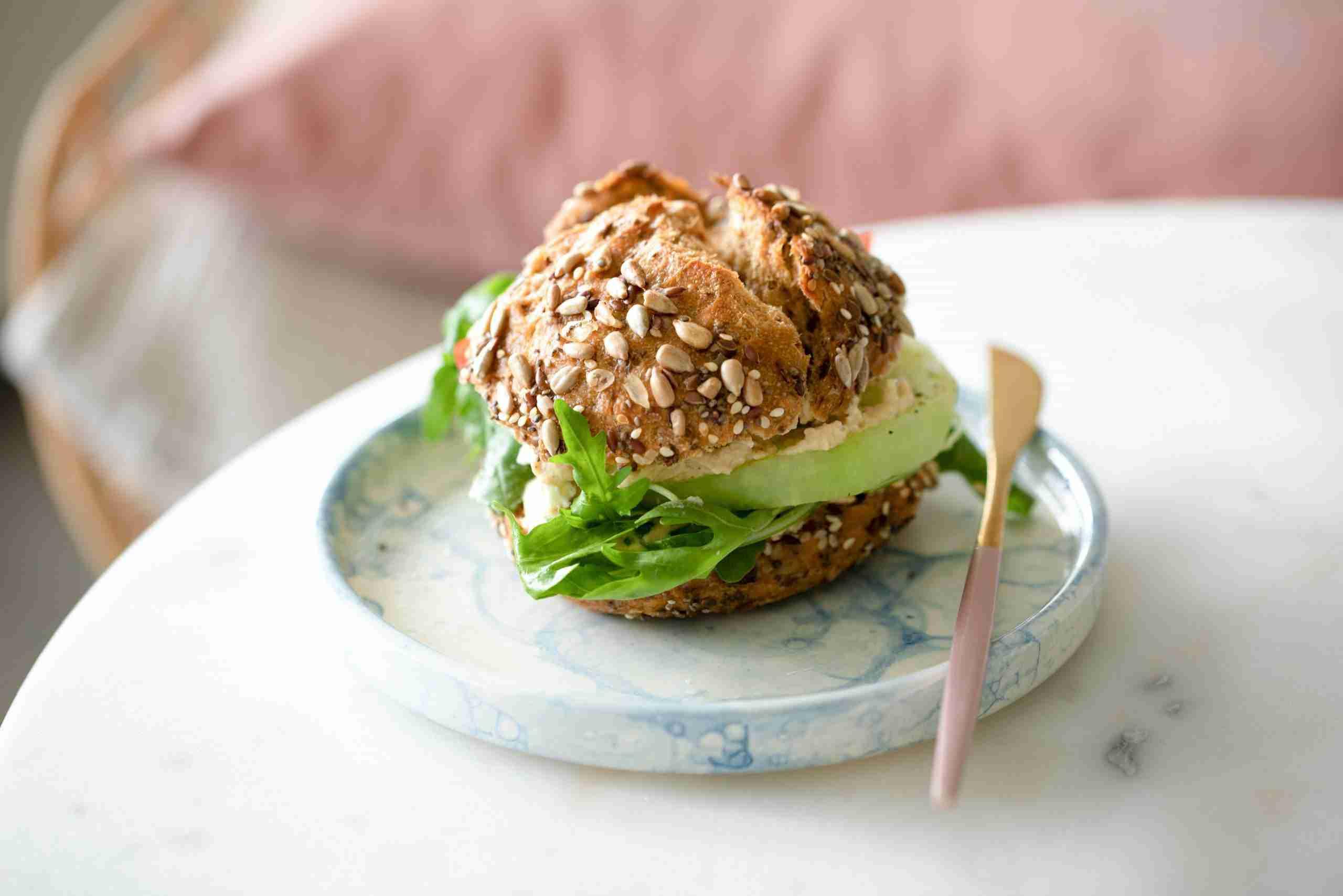 Sandwich on a whole grain seeded bun with lettuce and avocado.